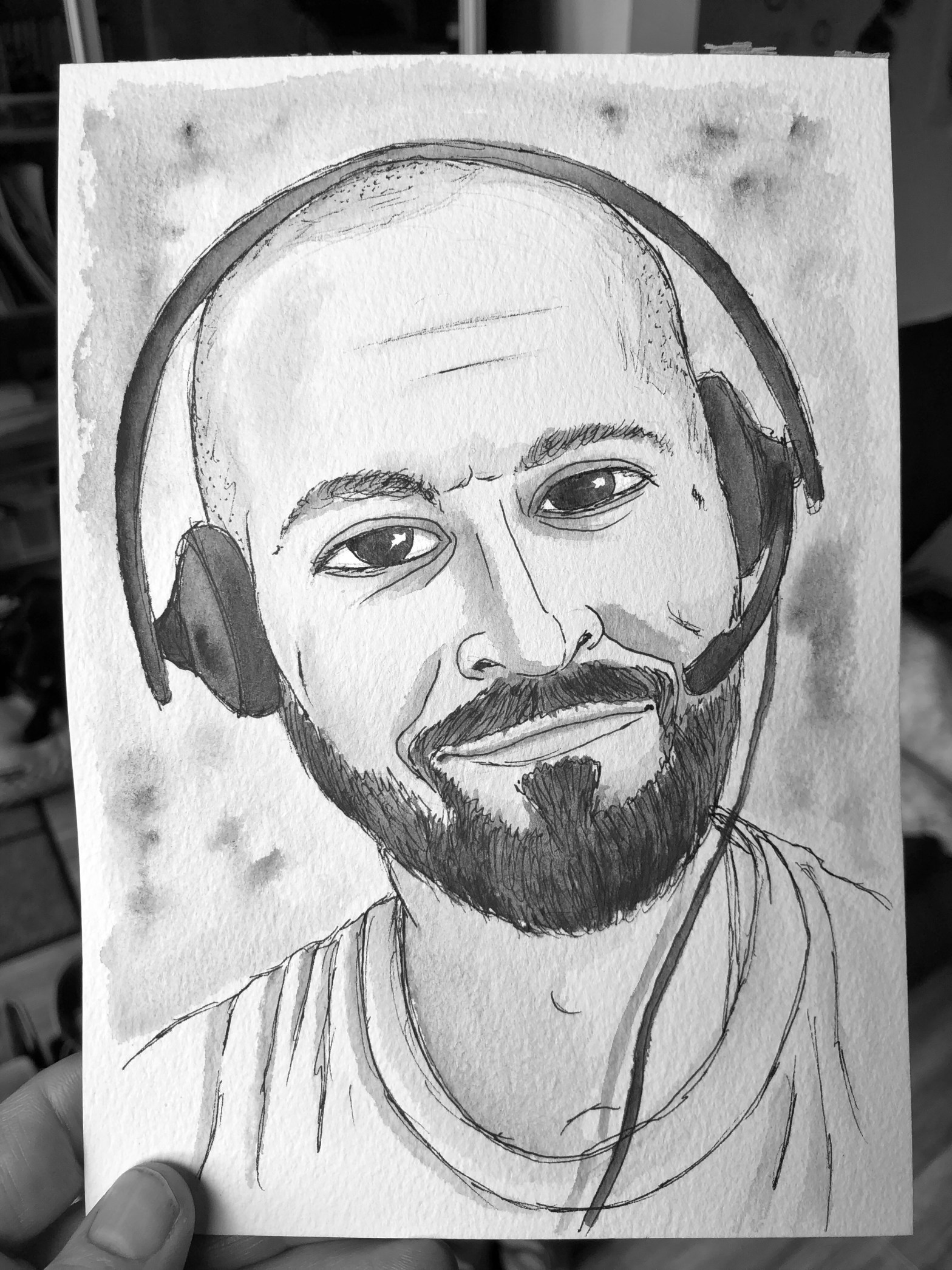 Watercolor and pen portrait of man with bald head and headset smiling.