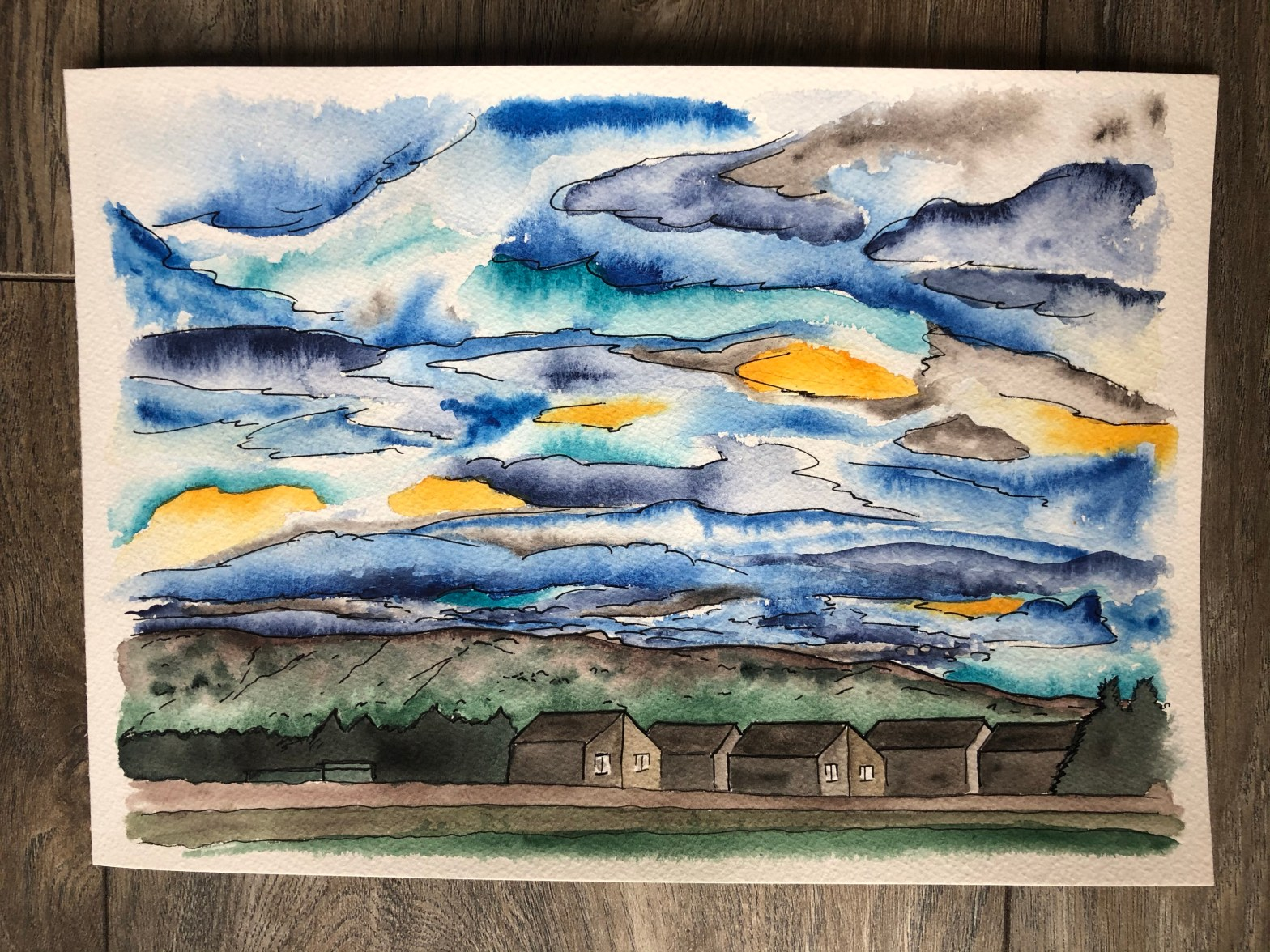 Watercolor painting of the morning sky in blue and yellow.